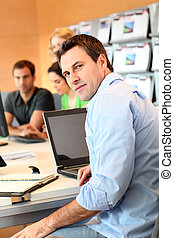 Man sitting in office in front of laptop computer