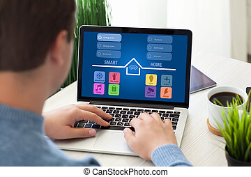 man sitting in room with notebook app smart home screen