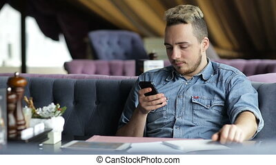 Man sitting in the restaurant , texting on mobile phone and smiling