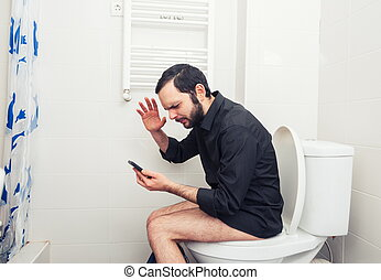 man sitting in toilet and talking on phone