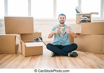 Man sitting in yoga pose, moving to new house