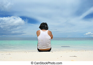 Man sitting lonely on beach - Asian young man sitting alone...