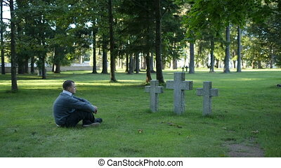 Man sitting mourning in front of three crosses