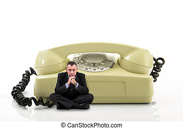 man sitting near an old phone