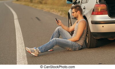 Man sitting near broken car with cell phone