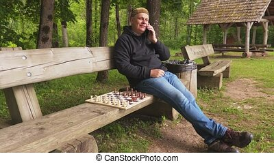 Man sitting near chessboard and talking on smartphone
