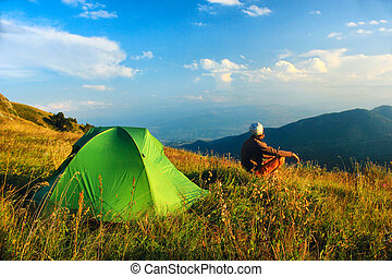 man sitting near tent in the mountains