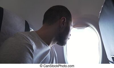 Man sitting near the window of flying airplane and listening to music on headphones with your smartphone. stock footage video