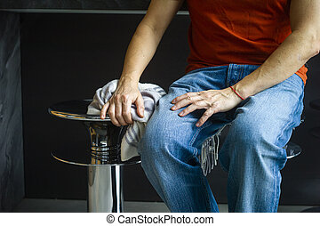 A man wearing casual sitting on a barstool, indoor cropped shot