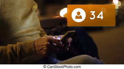Man sitting on a bench at night while typing on his phone 4k