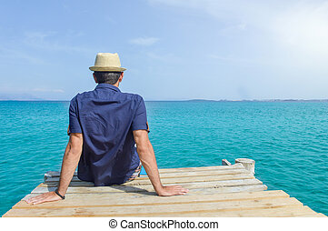 Man sitting on a dock at seaside