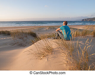 Man sitting on a dune and enjoying the scenery of a beach