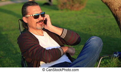 Man sitting on a park bench and talking on the smart phone