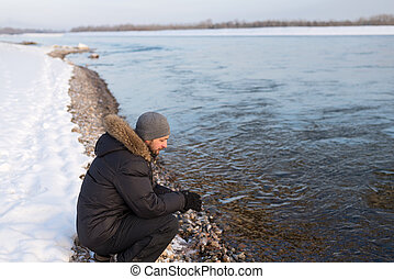 Man sitting on a river bank