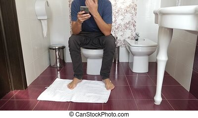 man sitting on a toilet and looking in the cell phone. 4k, slow motion