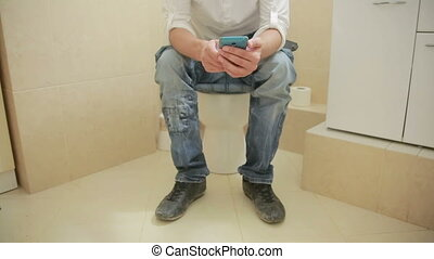 man sitting on a toilet and looks in the cell phone