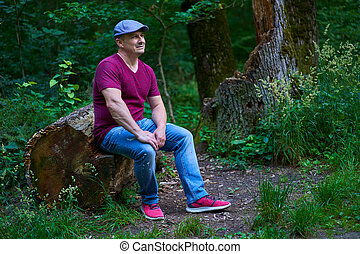 Man sitting on a tree trunk
