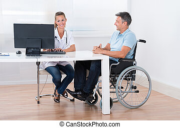Man Sitting On A Wheelchair Consulting With Doctor