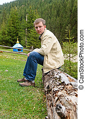Man sitting on an old tree trunk