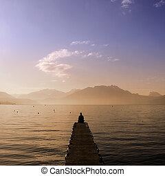 Man sitting on Annecy lake pontoon