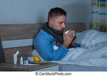 Man Sitting On Bed Drinking Cup Of Tea