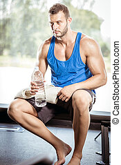 Man sitting on bench and drinking water