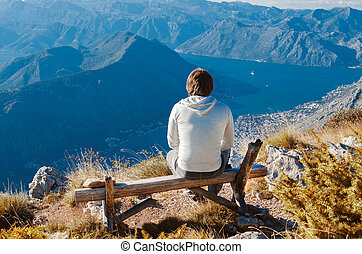 Man sitting on bench, high up in the mountains enjoying Beauty w