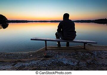 Man sitting on bench on lake shore at sunset