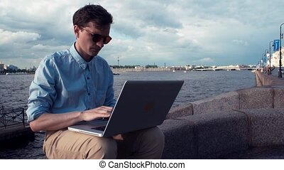 Man sitting on bench with laptop receiving good news and celebrating success