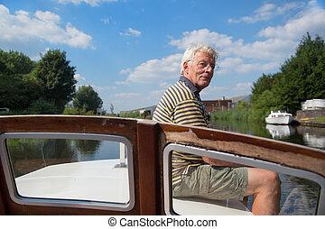 Man sitting on boat - Senior man making day trip on boat at...