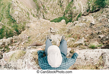 Man sitting on edge of cliff.