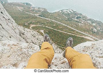 Man sitting on edge of cliff, pov.
