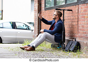 Man Sitting On Electric Scooter Taking Selfie