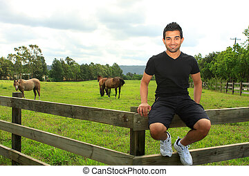 man sitting on fence of a horse paddock