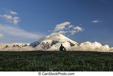 man sitting on field near active volcanoes of Kamchatka with snowy hills