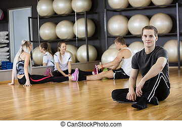 Man Sitting On Floor With Friends In Background At Gym