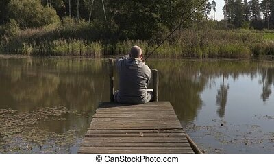 Man sitting on footbridge with fishing rod