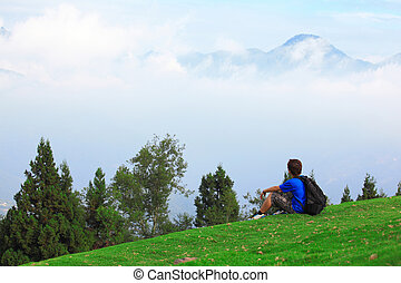 man sitting on grass and looking mountain