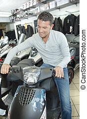 Man sitting on modern scooter