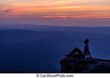 Man sitting on mountain peak at sunset with mountains background.