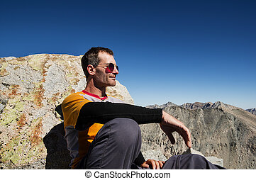 Man Sitting On Mountain Top