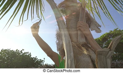 Man sitting on palm tree trying to get connection on his mobile phone, searching for civilization