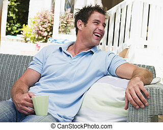 Man sitting on patio with coffee laughing