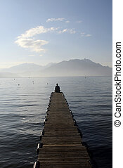 Man sitting on pontoon in front of lake annecy and mountains...