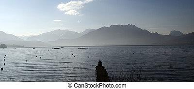 Man sitting on pontoon lake annecy - Man sitting on pontoon...