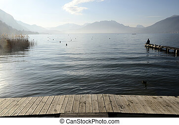 Man sitting on pontoon lake annecy - Man sitting on pontoon...