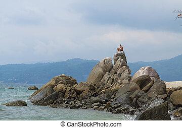 Man sitting on rock.