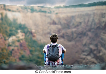 Man sitting on rocky cliff - Young tourist man with backpack...