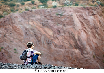 Man sitting on rocky cliff