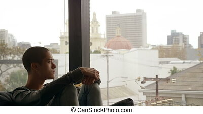 Man sitting on sofa near window at home 4k